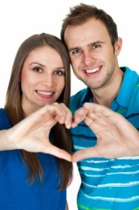 couple creating heart shape with their hands
