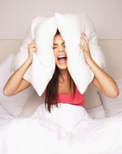 woman trying to use pillows to stop ringing in the ears