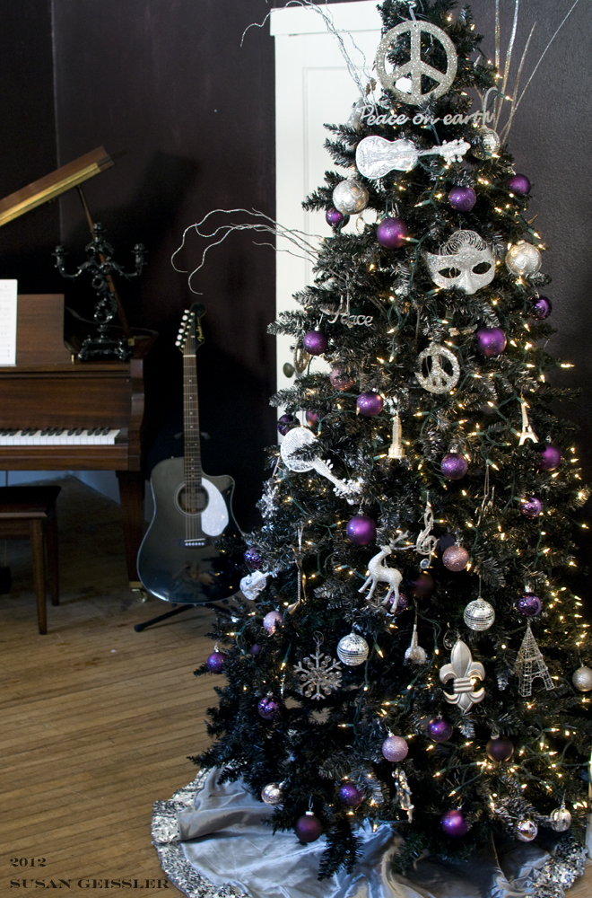 Black Christmas tree with purple and white ornaments.