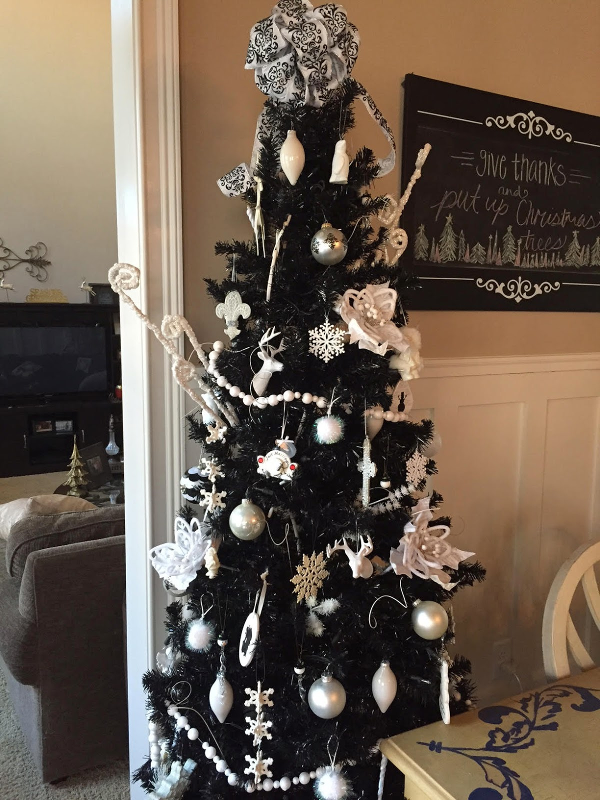 Black Christmas tree with white Christmas decorations.