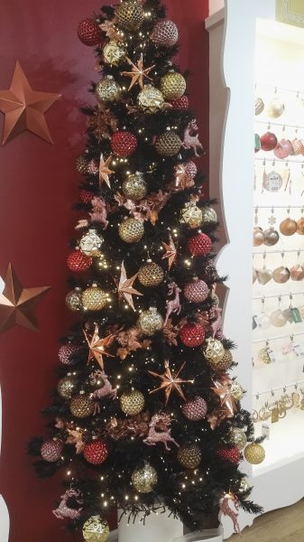 Black Christmas tree with rose gold and copper glass hexagon dimple balls.