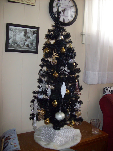 Black Christmas tree adorned with white snowflakes and gold Christmas ornaments.