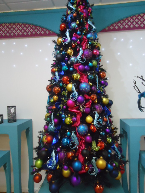 Black Christmas tree with multi-color Christmas decorations.