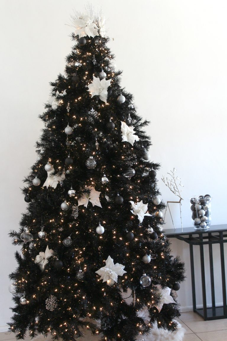 Gorgeously decorated black Christmas tree with jeweled white poinsettia ornaments.