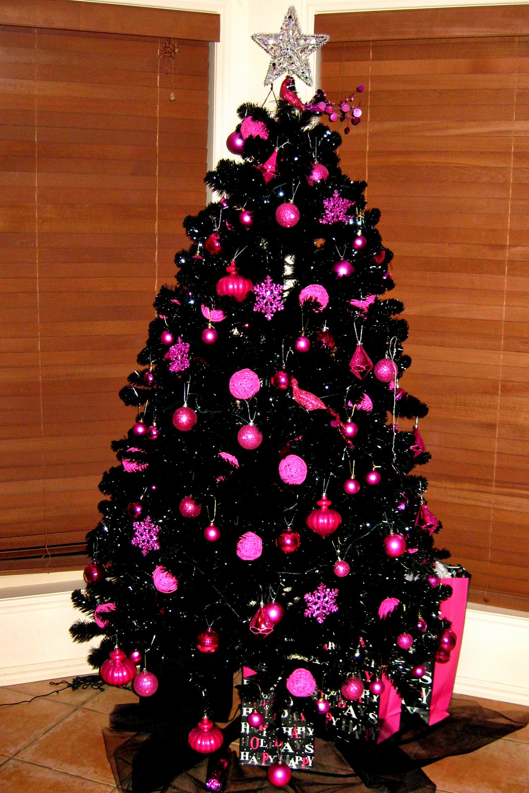 Black Christmas tree decorated in hot pink ornaments.