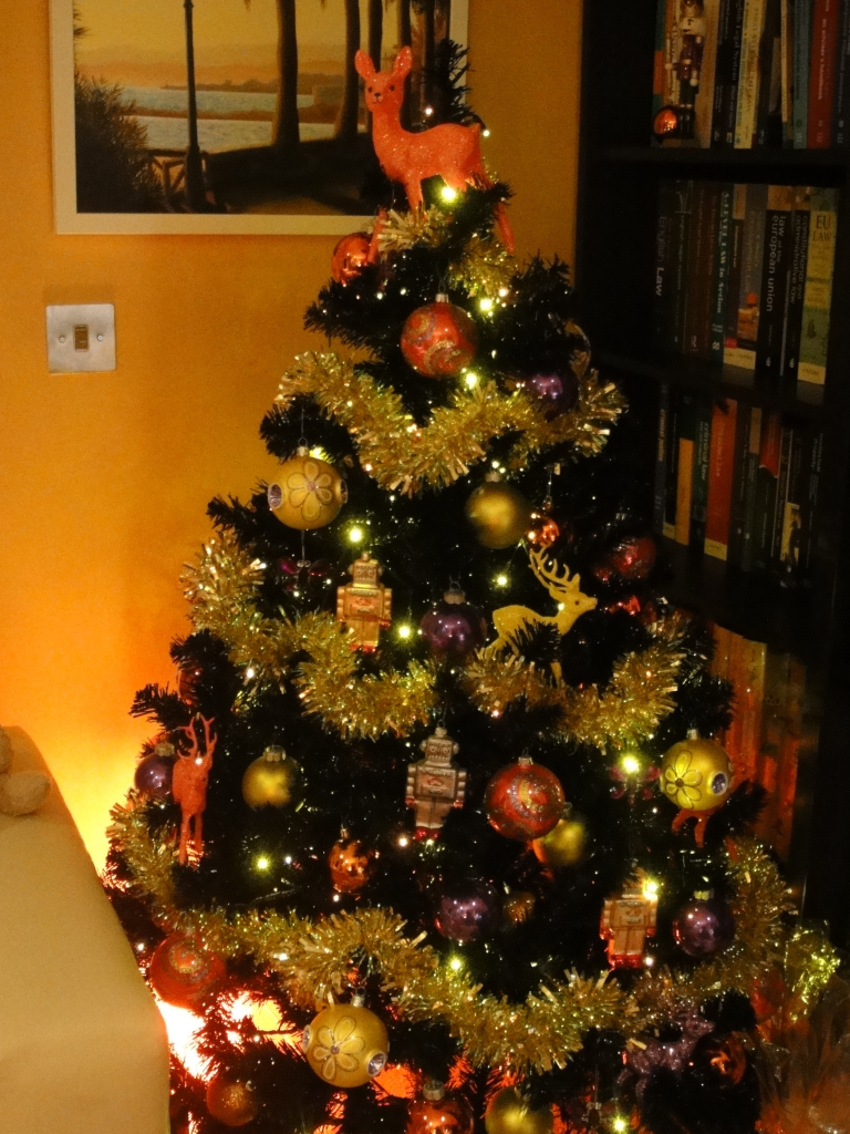 Black Christmas tree decorated in yellow and orange.